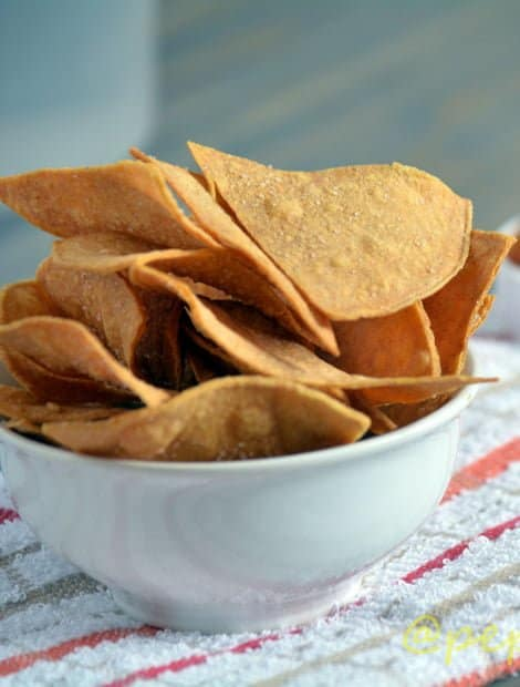 Spicy tortilla chips served in a white bowl.
