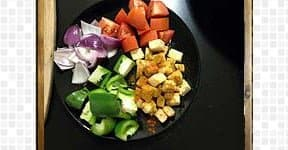 Diced onion, tomato, green bell pepper, and paneer cubes are kept in the black plate.