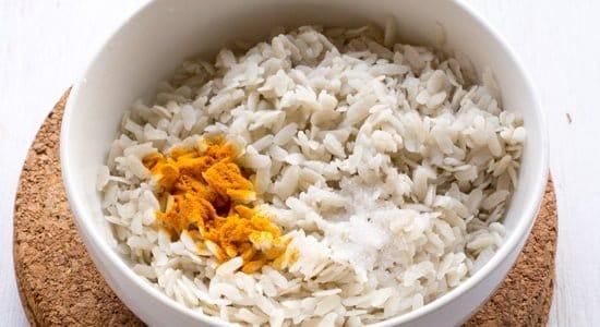 adding turmeric and salt to soaked poha