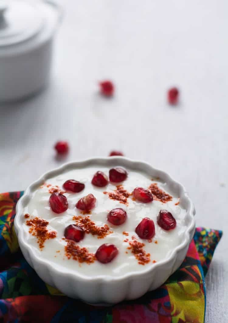 Pomegranate Raita made with yogurt / curd, fresh pomegranate arils and chili powder. This recipe is simple and quick to make. This raita tastes ultimately delicious and it is creamy, sweet and also spicy. Perfect to serve as side dish for rice or roti.