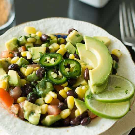 Black bean corn avocado salad lime cilantro dressing, a bright refreshing salad for serving as a side or appetizer. A great effortless addition for weeknight dinners or for game days. A paleo, gluten free and low carb dish made with vegetables and beans.