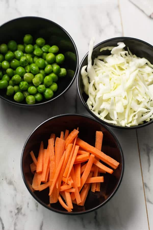 thin cut vegetables are in black bowls.