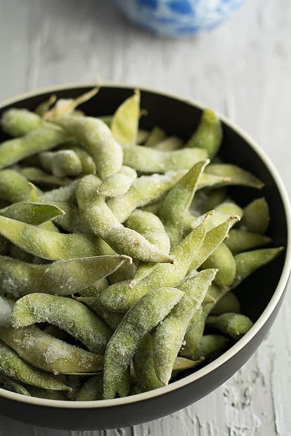 frozen edamame ready to steam in balck bowl for making spicy garlic edamame..