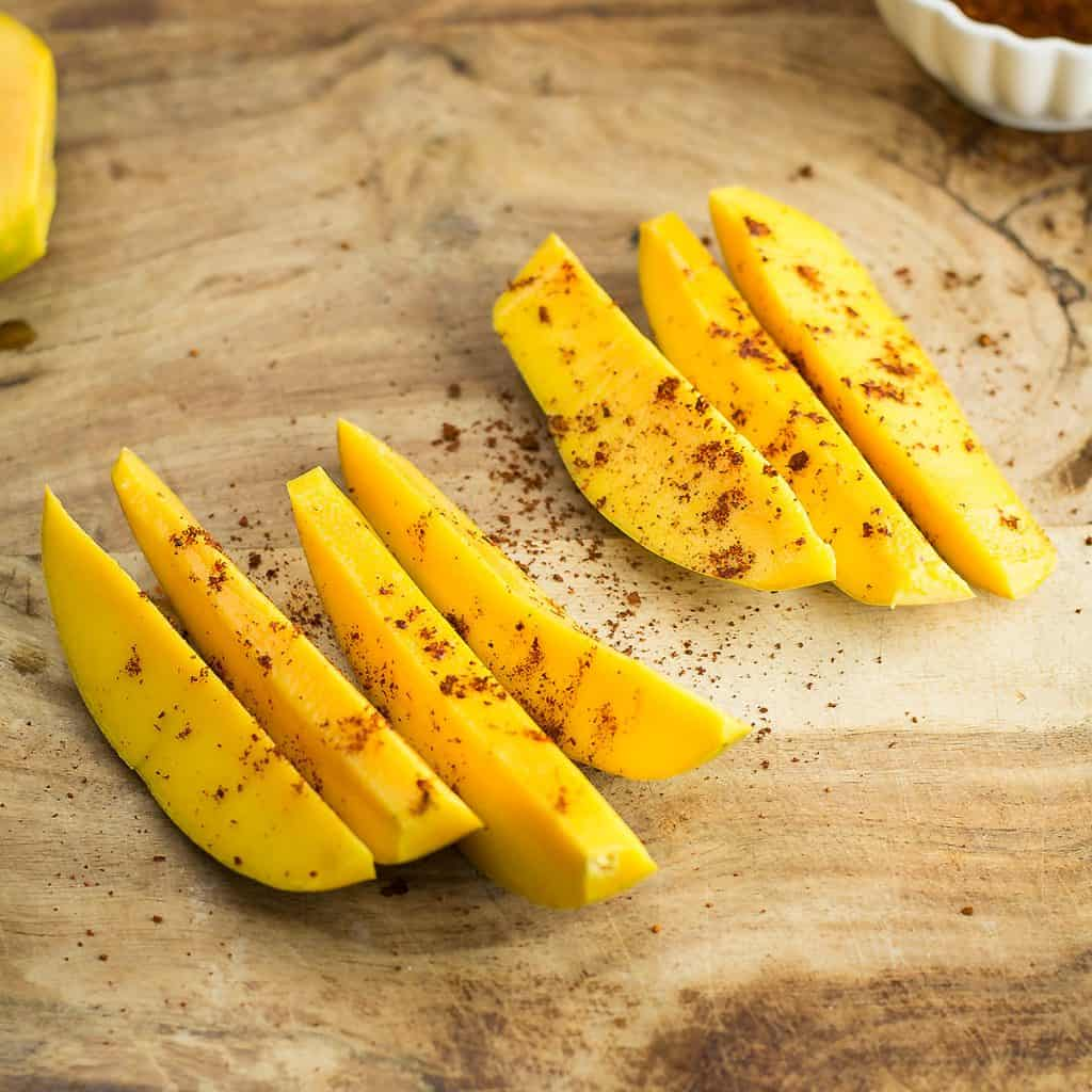 Chop the mango wedges and sprinkle chili powder, salt, and lime juice to make a spicy Mexican style fruit snack.