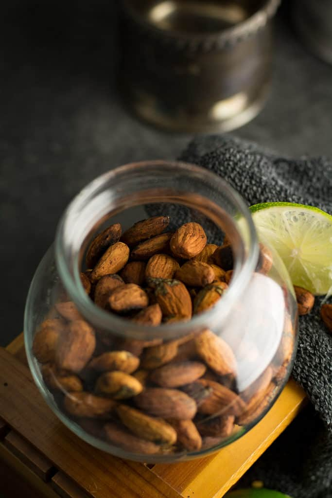 the chili and lime coated almonds in the clear jar with top view.