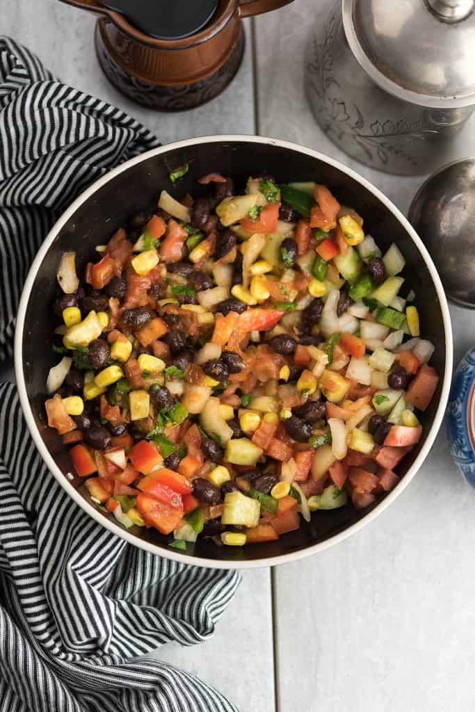 This Fiesta salad recipe is a crowd-pleasing dish. This Mexican style salad is delicious with bright flavors, made with corn, black bean, and red peppers.