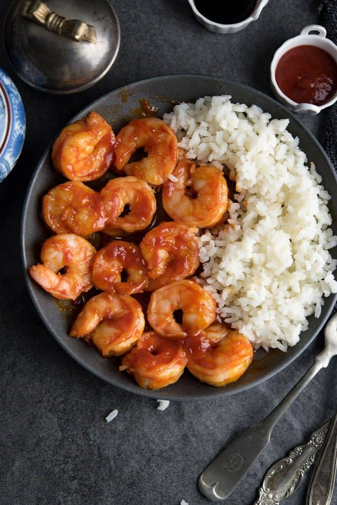 Honey Sriracha shrimp is placed over a black plate and served with rice.