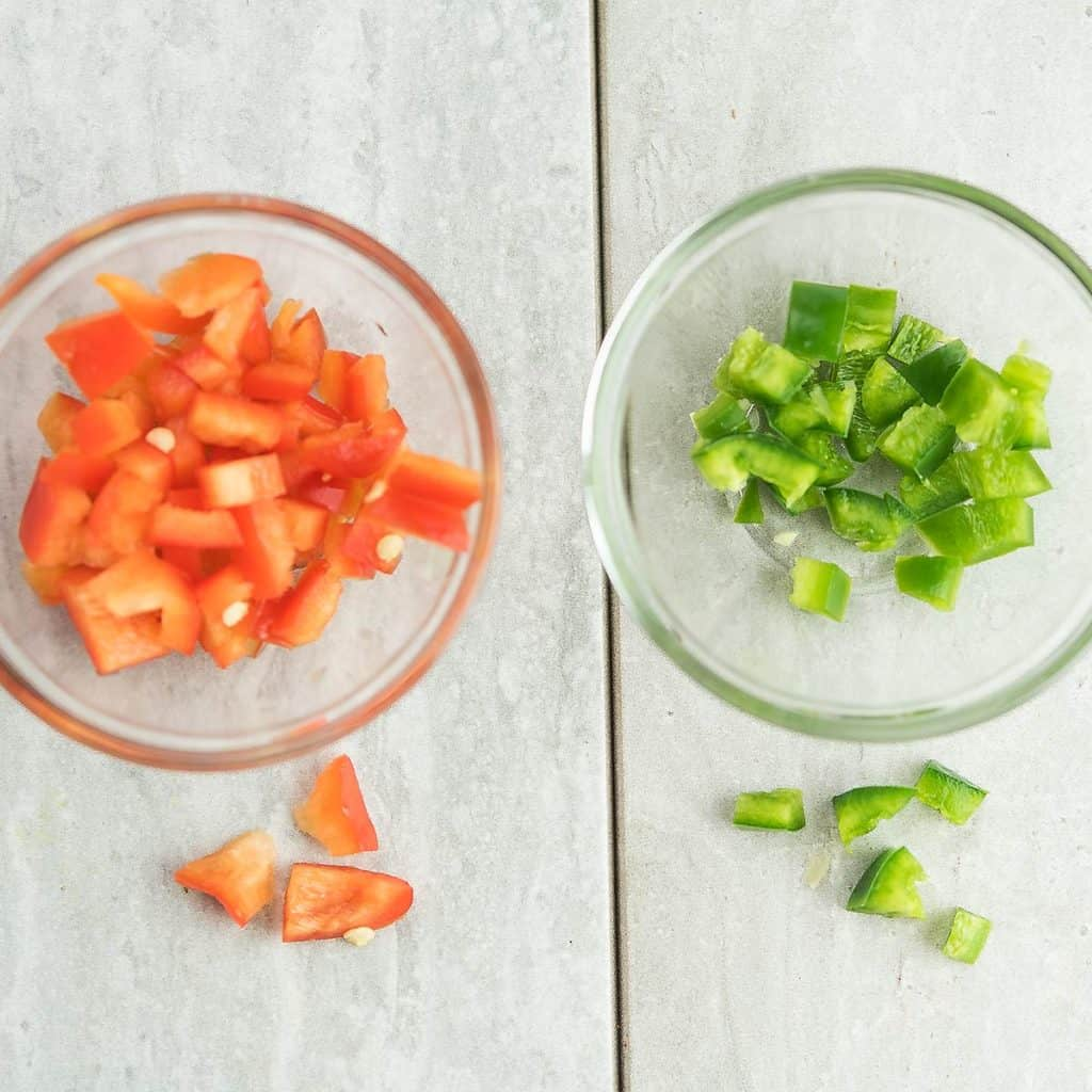 red pepper and jalapeno are chopped, in a clear bowl for prepping fiesta corn salad