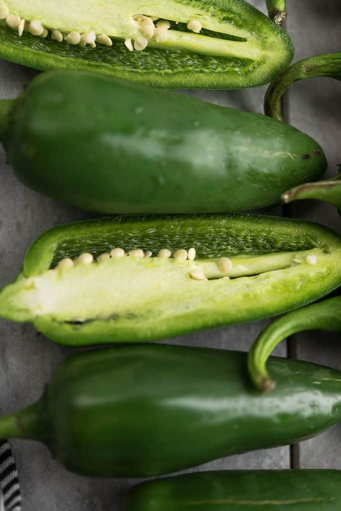 The chopped and cut hot peppers are arranged in a row.