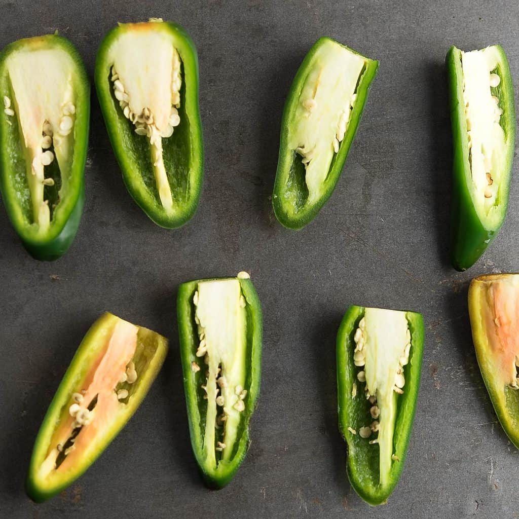 Jalapeno peppers are halfed and ready to core.