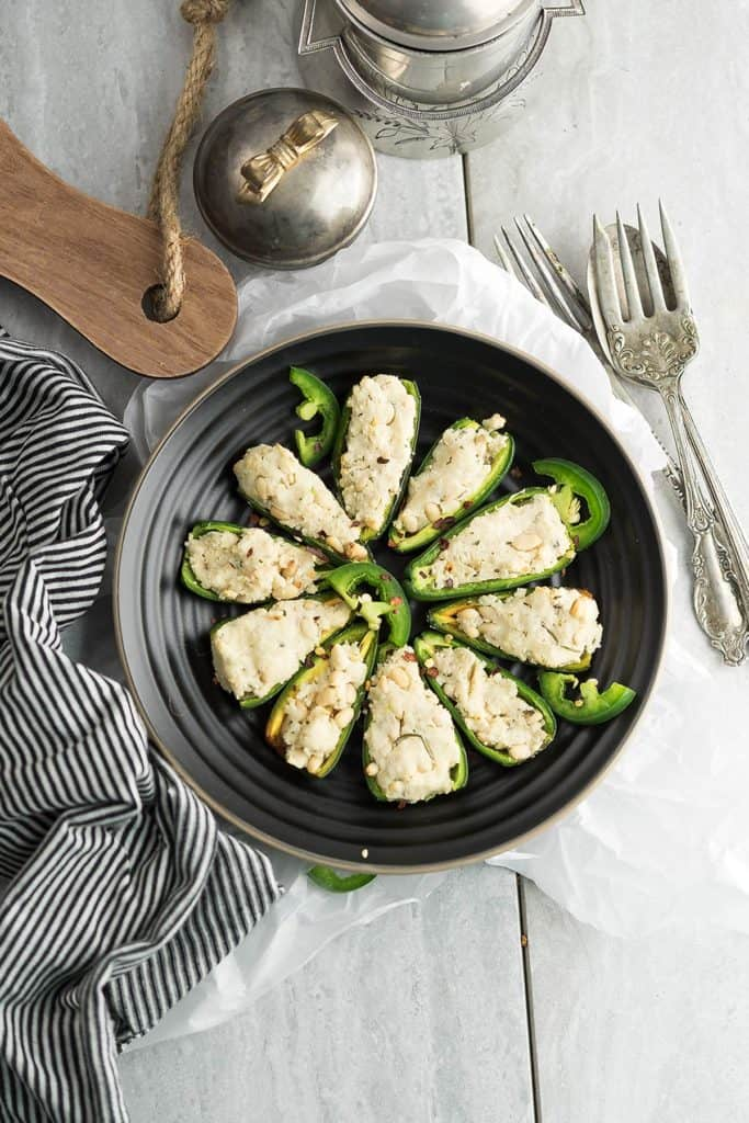 Dairy free vegan jalapeno poppers are served in a decorative black plate.