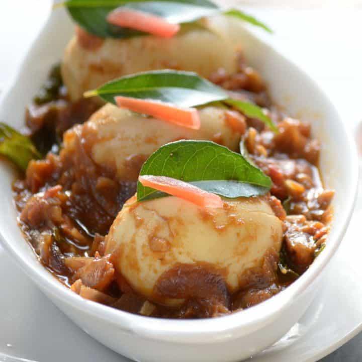 Chittinad egg gravy, served in white bowl.