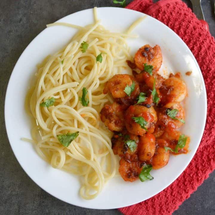 sriracha shrimp pasta in a white plate.